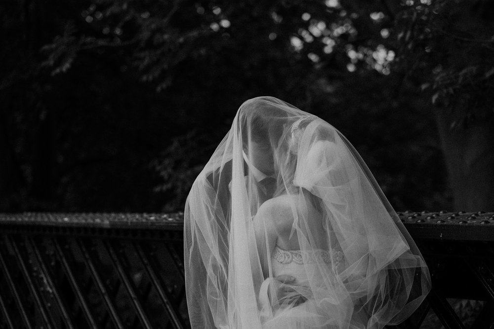 Black and white photo of bride and groom under bride's veil