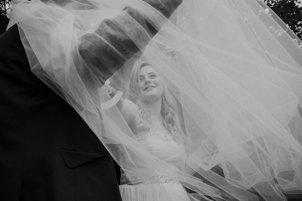 Black and white photo of bride and groom smiling under bride's veil