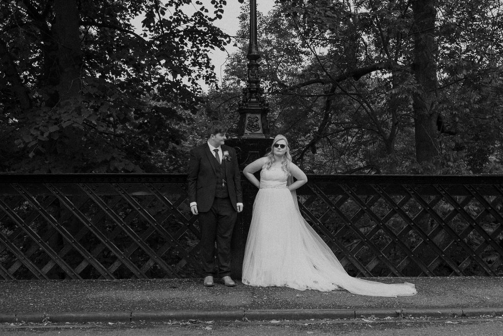 Black and white photo of bride and groom standing on bridge, bride wearing sunglasses