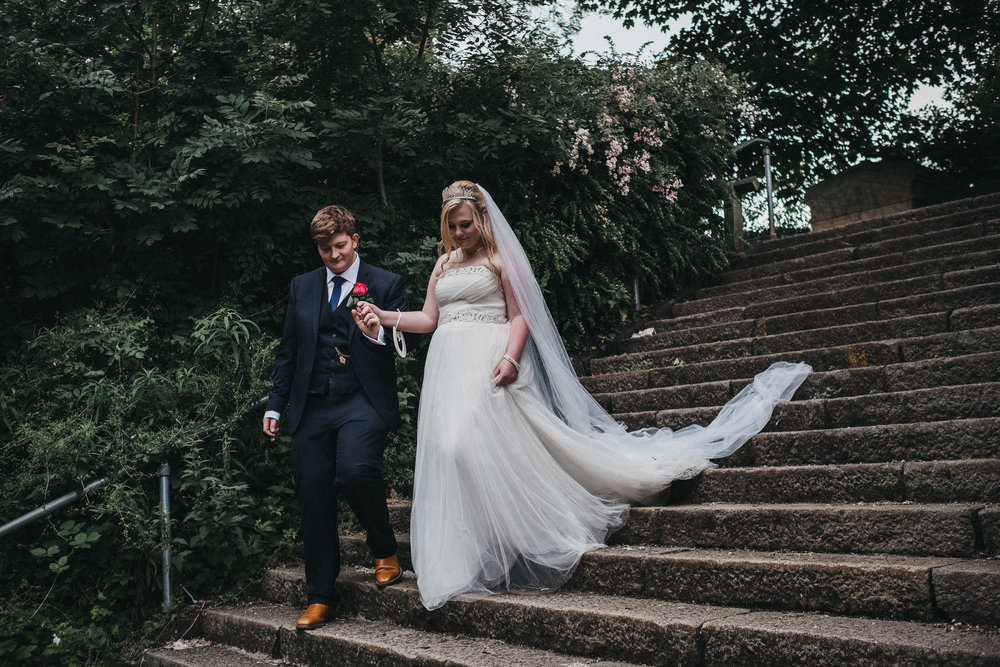 Groom holds bride's hand as they walk down stairs