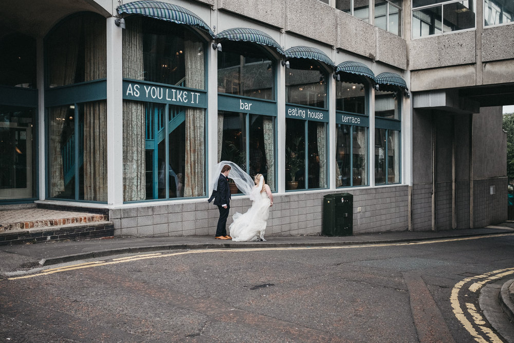 Bride's veil blows into groom's face outside wedding venue