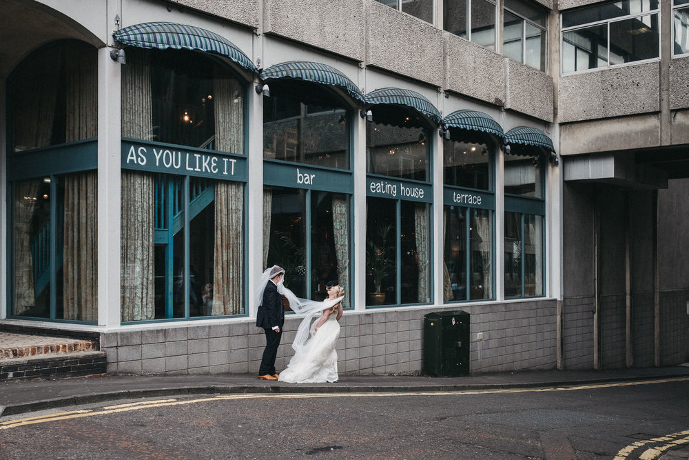 Bride laughs as wind blows veil over groom's head