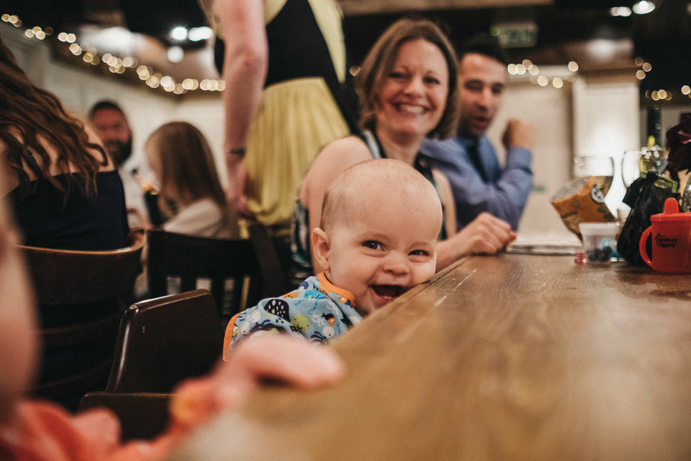 Baby laughs while leaning on table