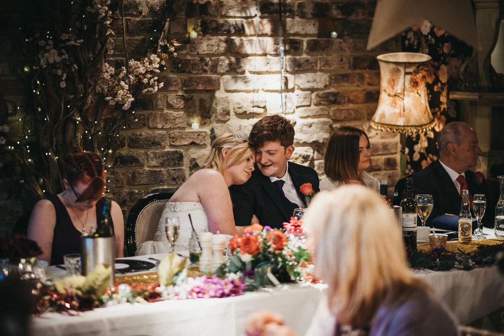 Bride hugs groom at top table