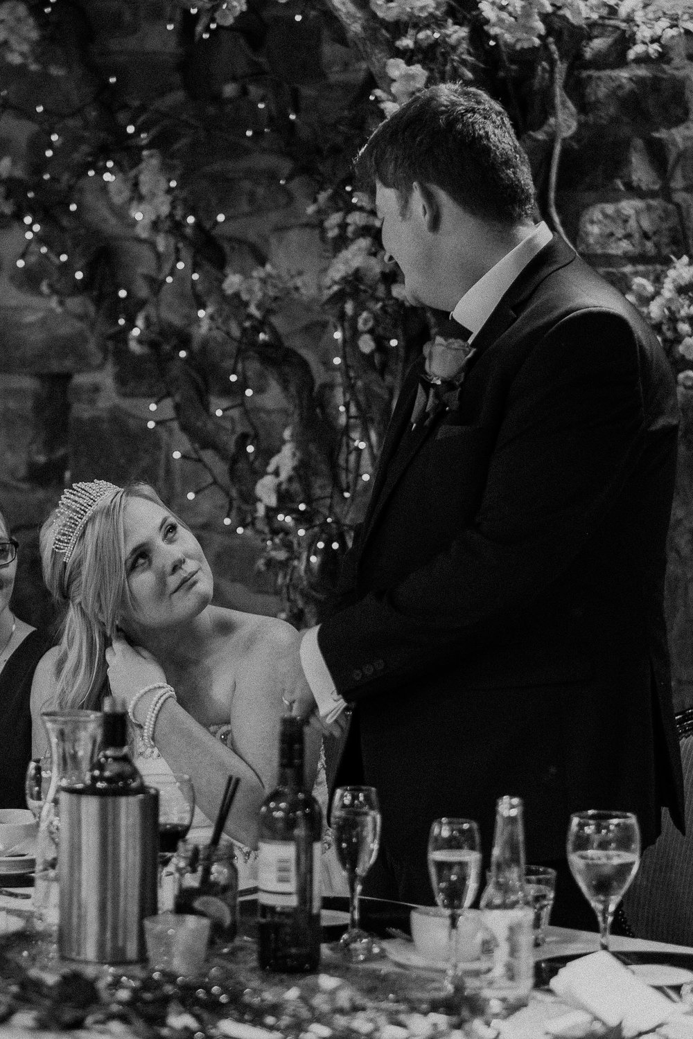 Black and white photo of bride and groom looking at each other lovingly during speeches