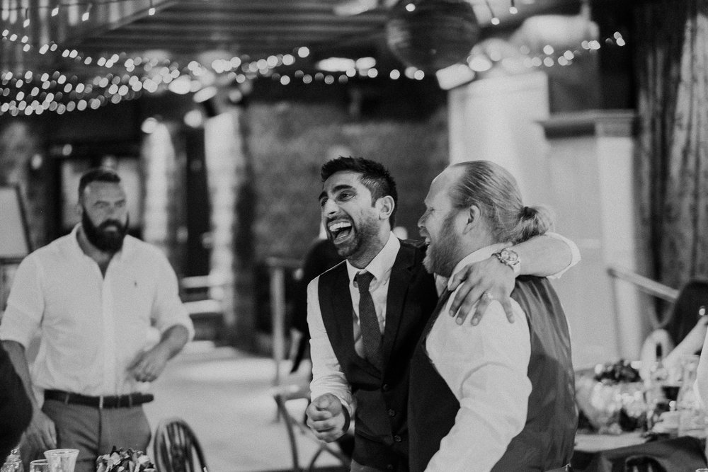 Black and white photo of wedding guests roaring with laughter after speeches