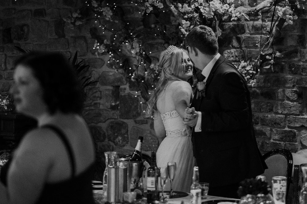 Black and white photo of bride and groom hugging and laughing at As You Like It