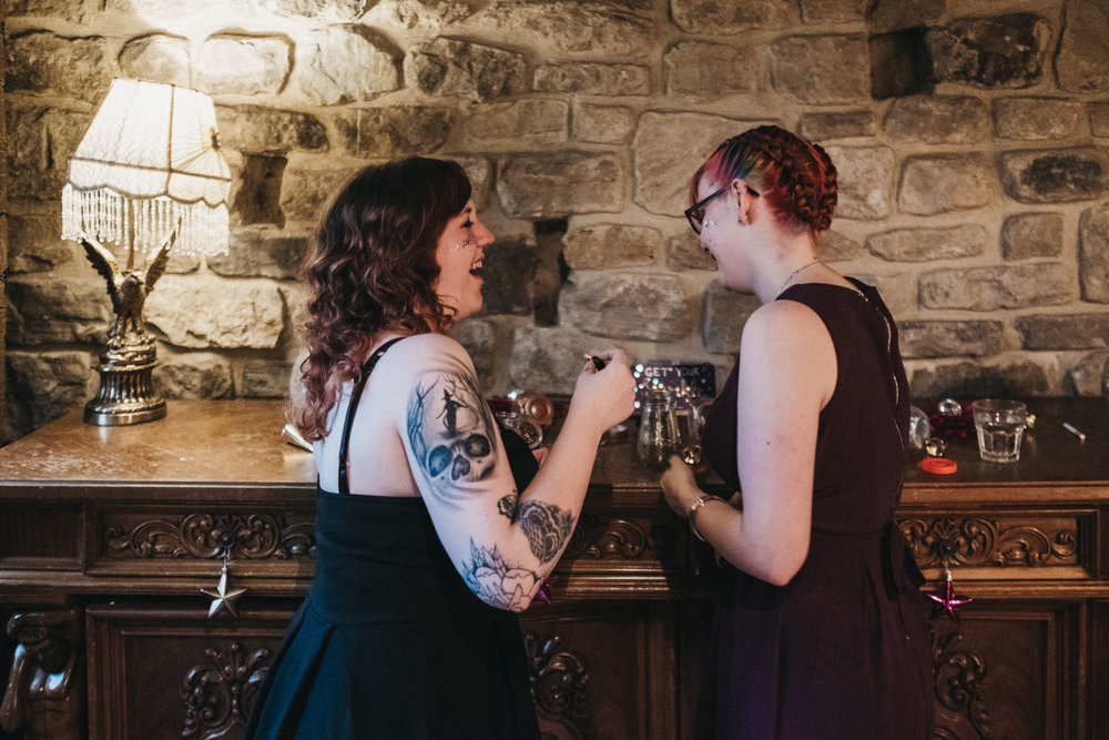 Bridesmaid with tattoos laughing while applying glitter makeup