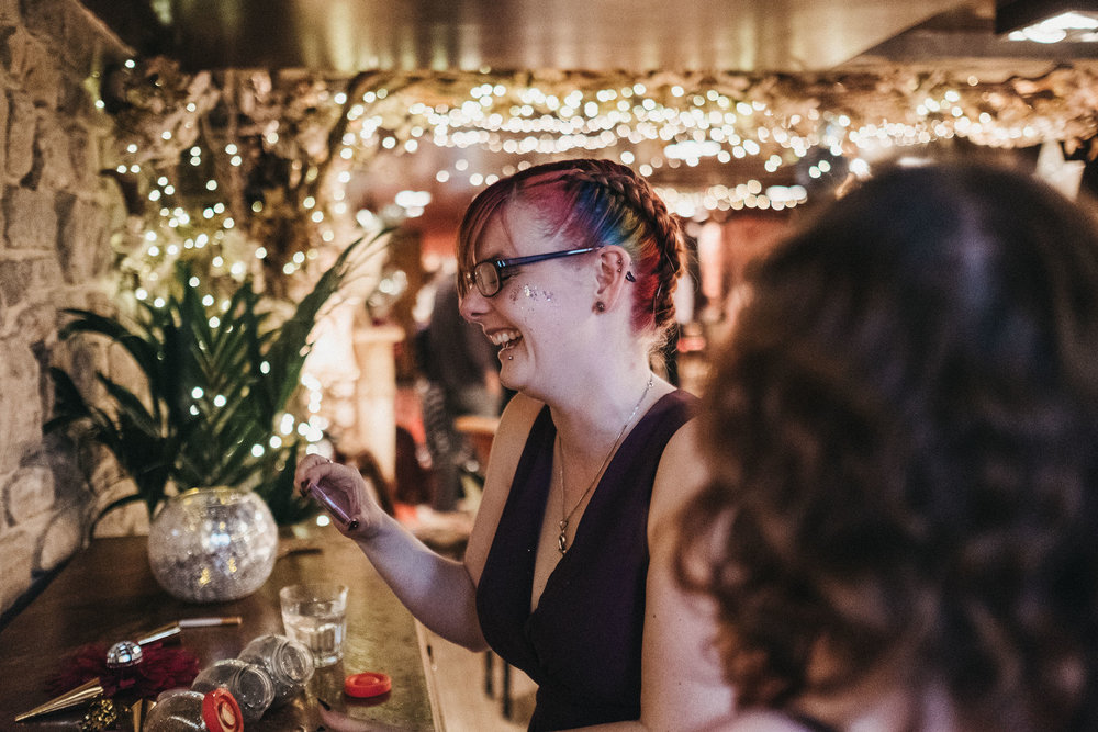 Bridesmaid with rainbow hair and glitter makeup laughs with fairy lights behind