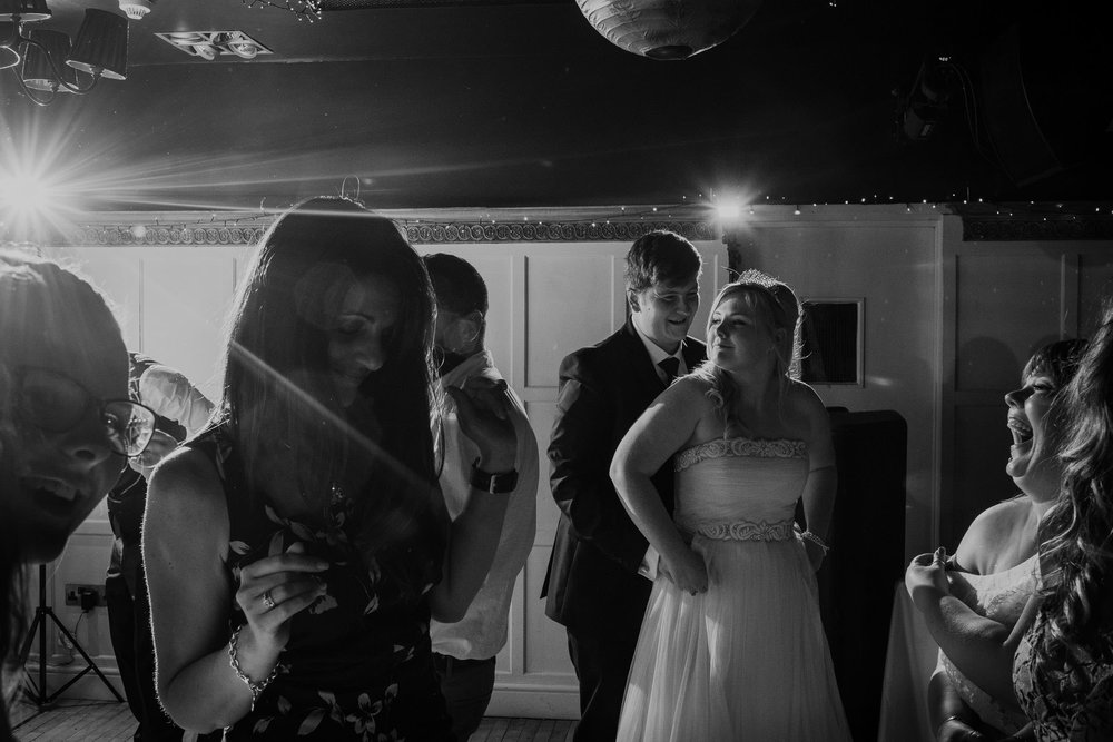 Black and white photo of bride and groom dancing with wedding guests
