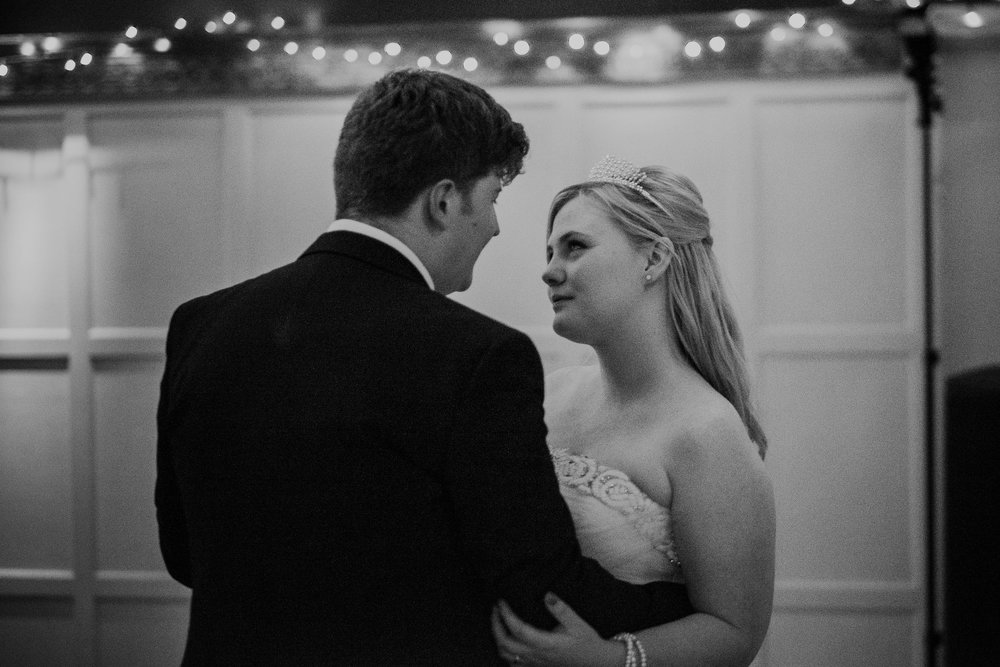 Black and white photo of bride looking intensely at groom during first dance