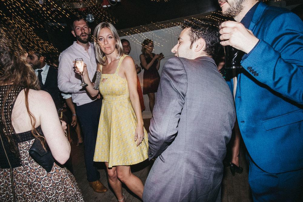 Wedding guest walks through busy wedding dance floor carrying wine glass
