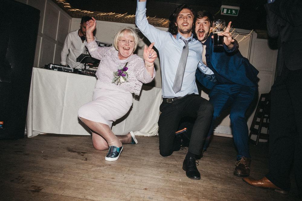Wedding guests and bride's mam kneel down on dance floor