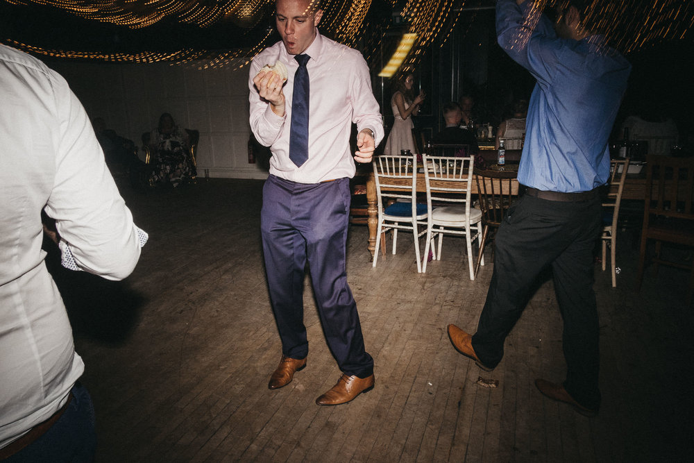 Wedding guest looks at burger while on dance floor
