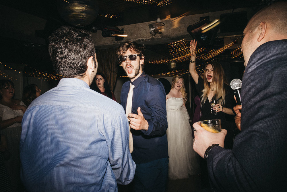 Wedding guest dances with sunglasses on with bride in background