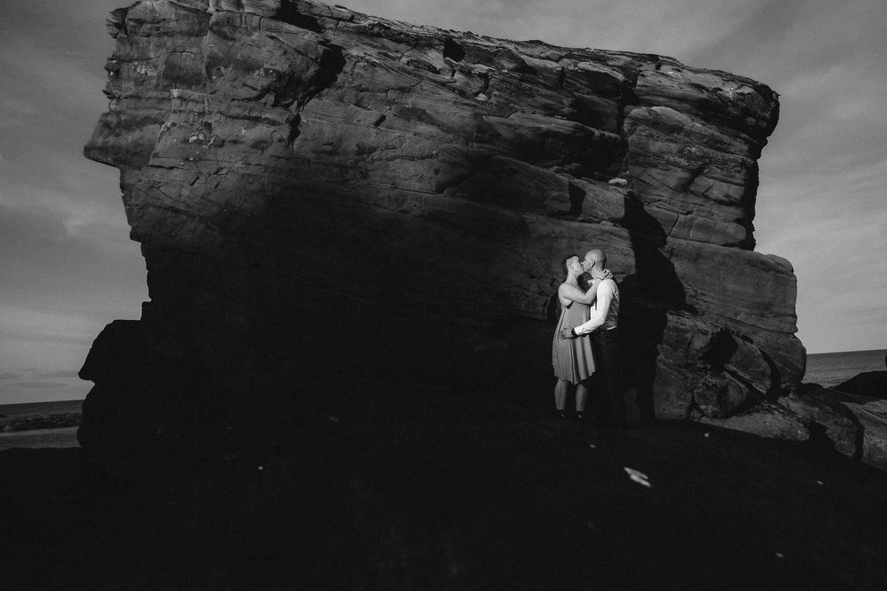 Back and white photo of couple kissing with Rocky Island behind