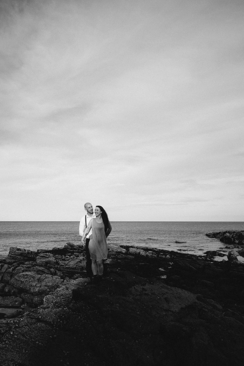 Back and white photo of couple cuddling on rocky beach