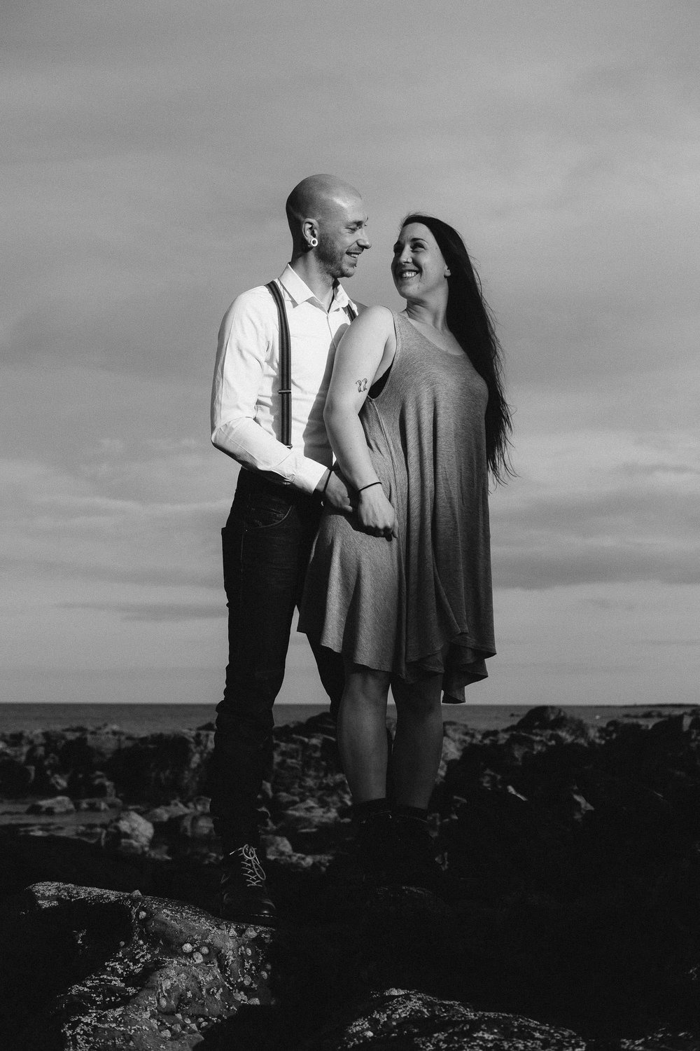 Back and white photo of couple smiling at each other on rocky beach