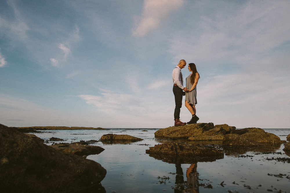 Couple holding hands while standing on rock at Seaton Sluice