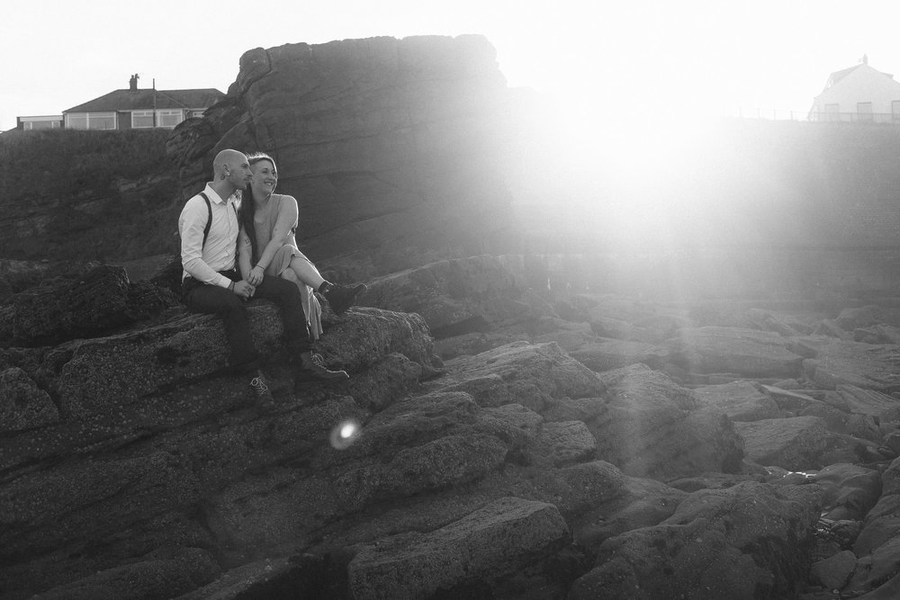 Back and white photo of couple sitting on rocks in strong sunlight