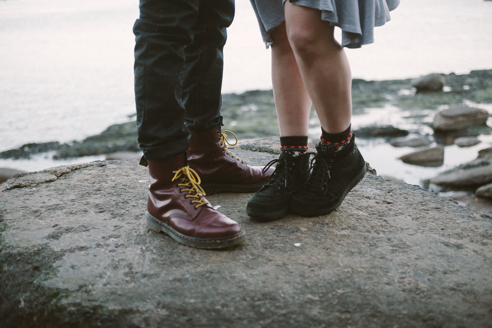 Close up of couple's shoes standing on rock