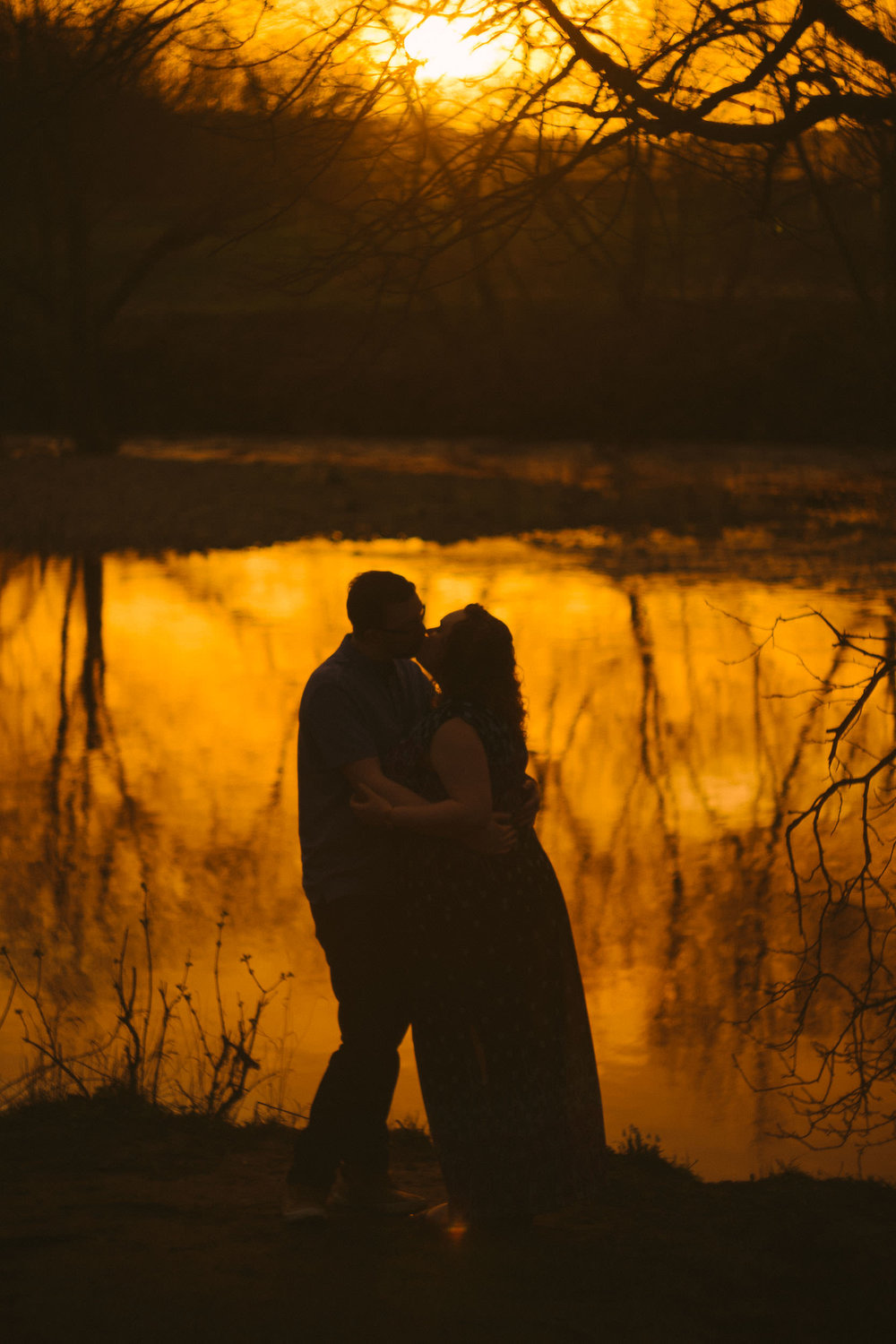 Silhouettes of a couple kissing with golden sunset reflected in water behind them