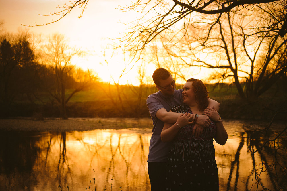 An engaged couple cuddling with trees and water in the background drenched in golden sunshine