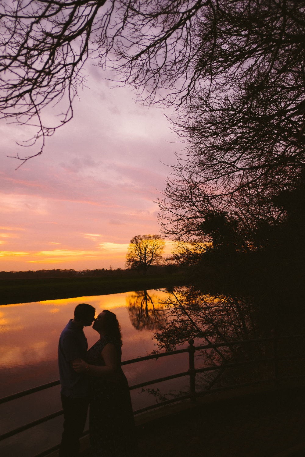 Silhouettes of a couple kissing by a river with a purple and gold sunset in the background
