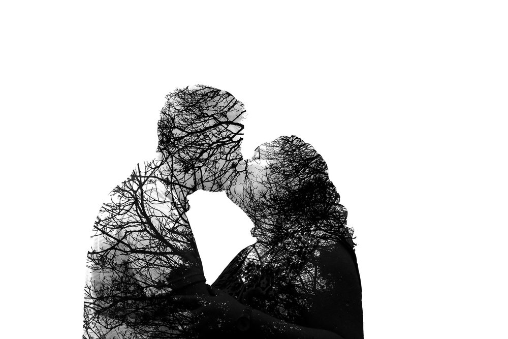 A black and white double exposure photo of a couple kissing with the silhouette of trees inside them
