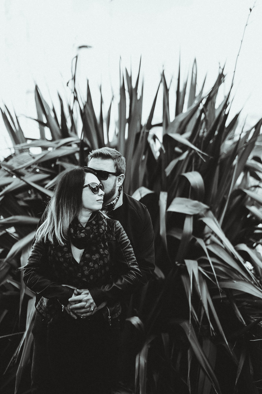A black and white photo of a couple cuddling with a large spiky plant behind them