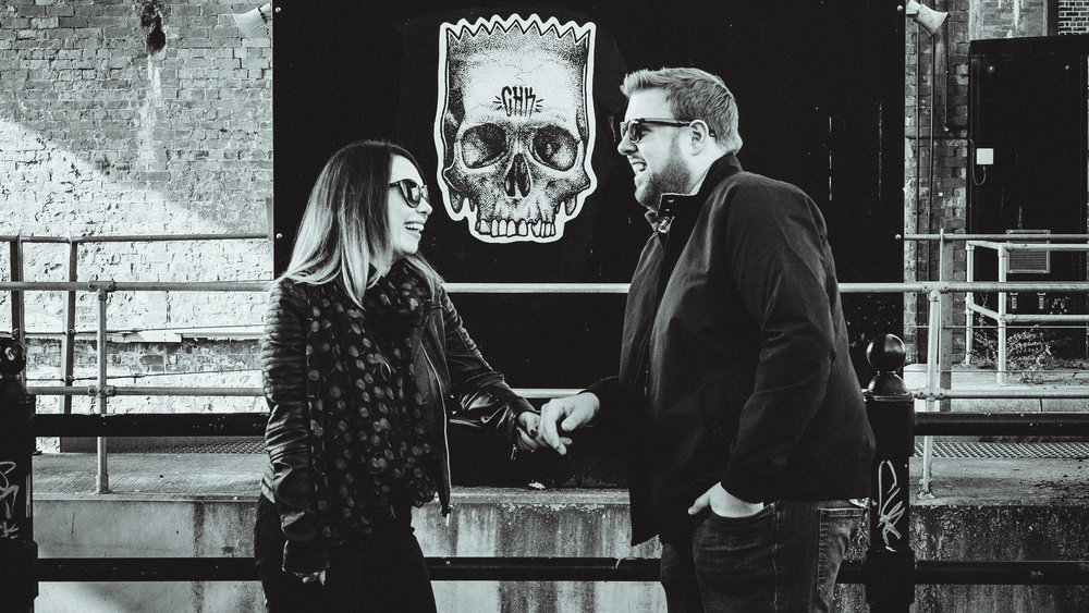 A black and white photo of a couple chatting in the Ouseburn with graffiti in the background