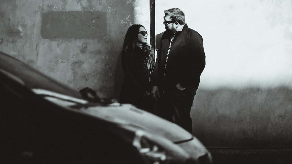 A black and white photo of a couple standing against a wall bathed in shadow with a car passing