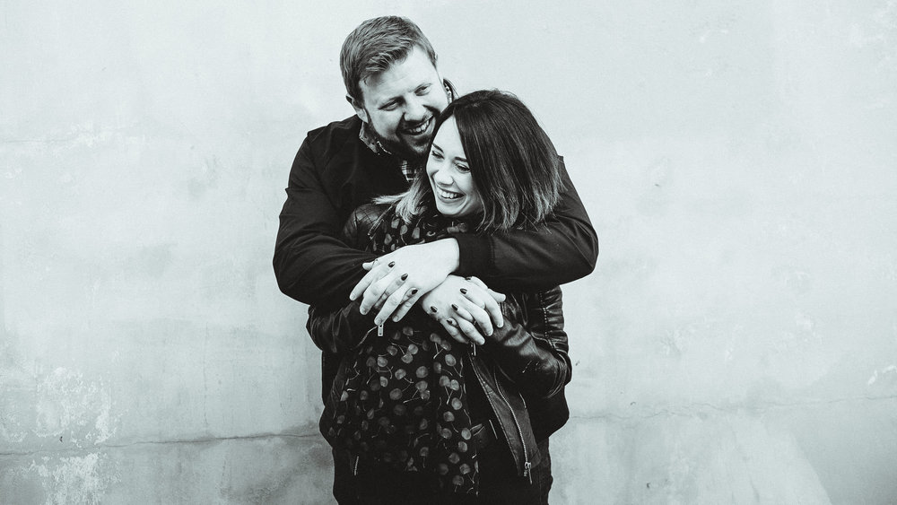 A black and white photo of a couple cuddling and giggling in front of a textured wall