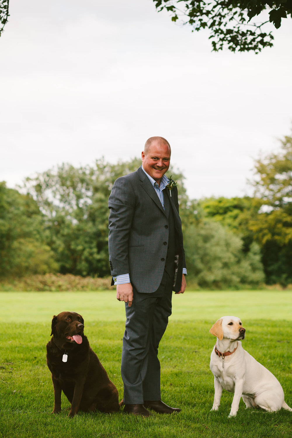 Groom poses with his two dogs before his wedding ceremony