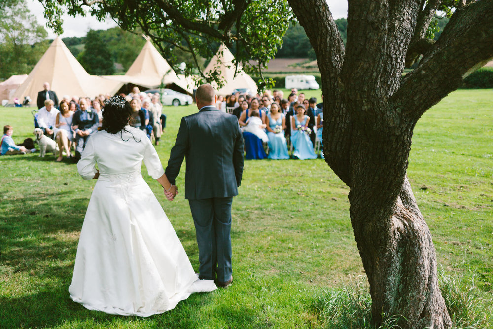 Bride and groom hold hands while looking at their guests during an outdoor wedding ceremony