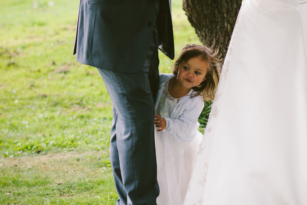Bride and groom's daughter peeks out from parents legs during wedding ceremony