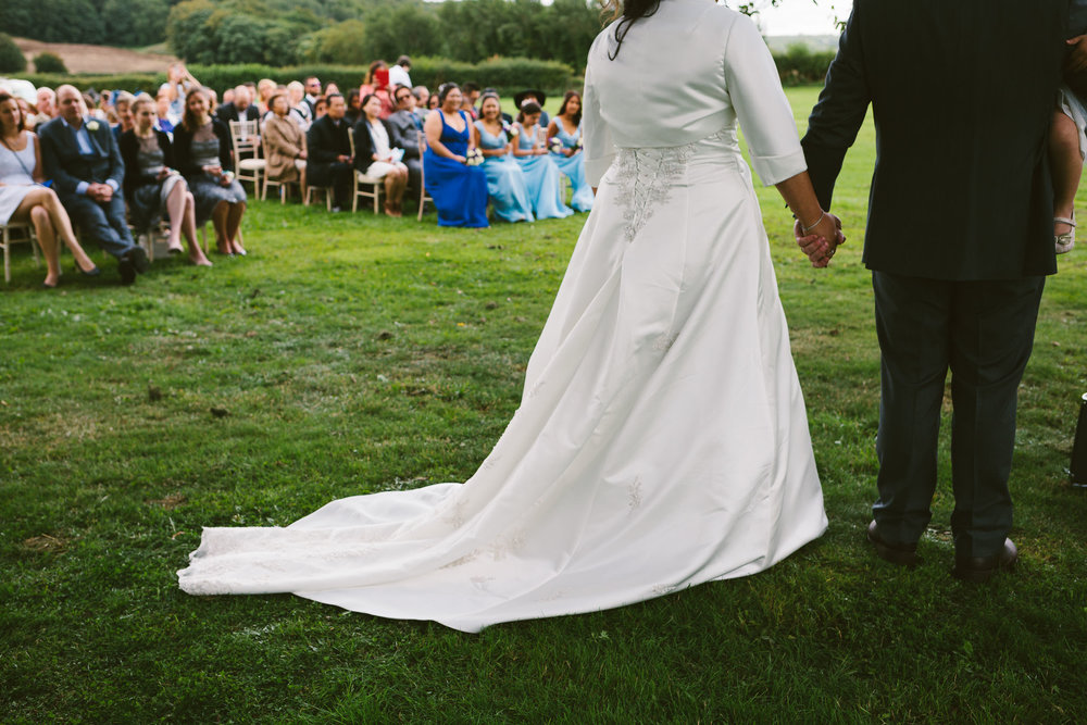 Bride and groom hold hands with wedding guests in background