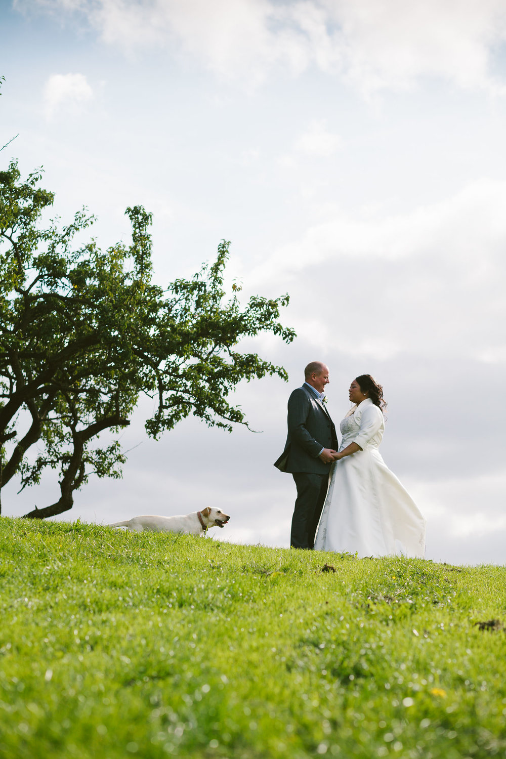 Bride and groom in romantic pose while dog photo bombs them