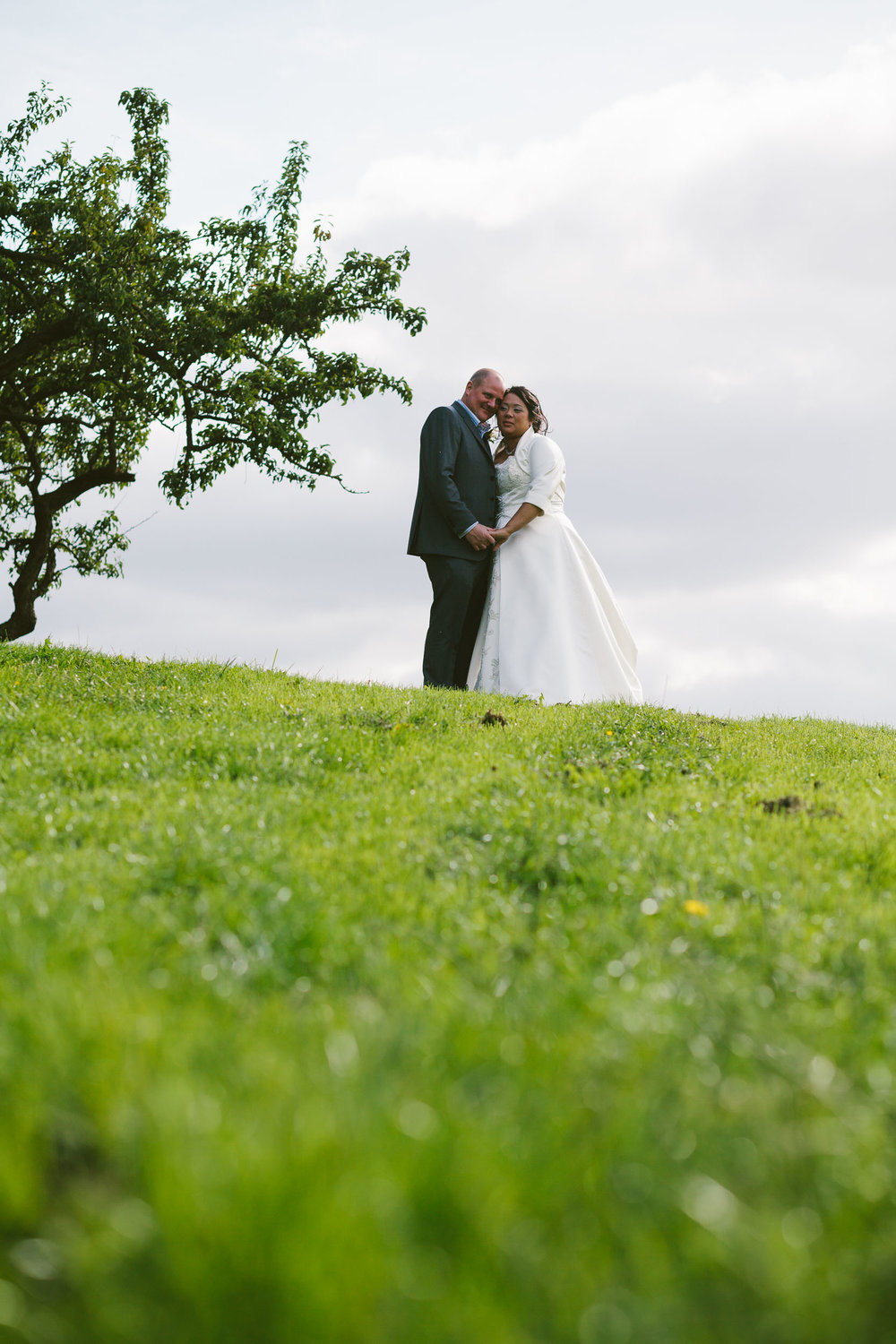 Bride and groom cuddle in green field