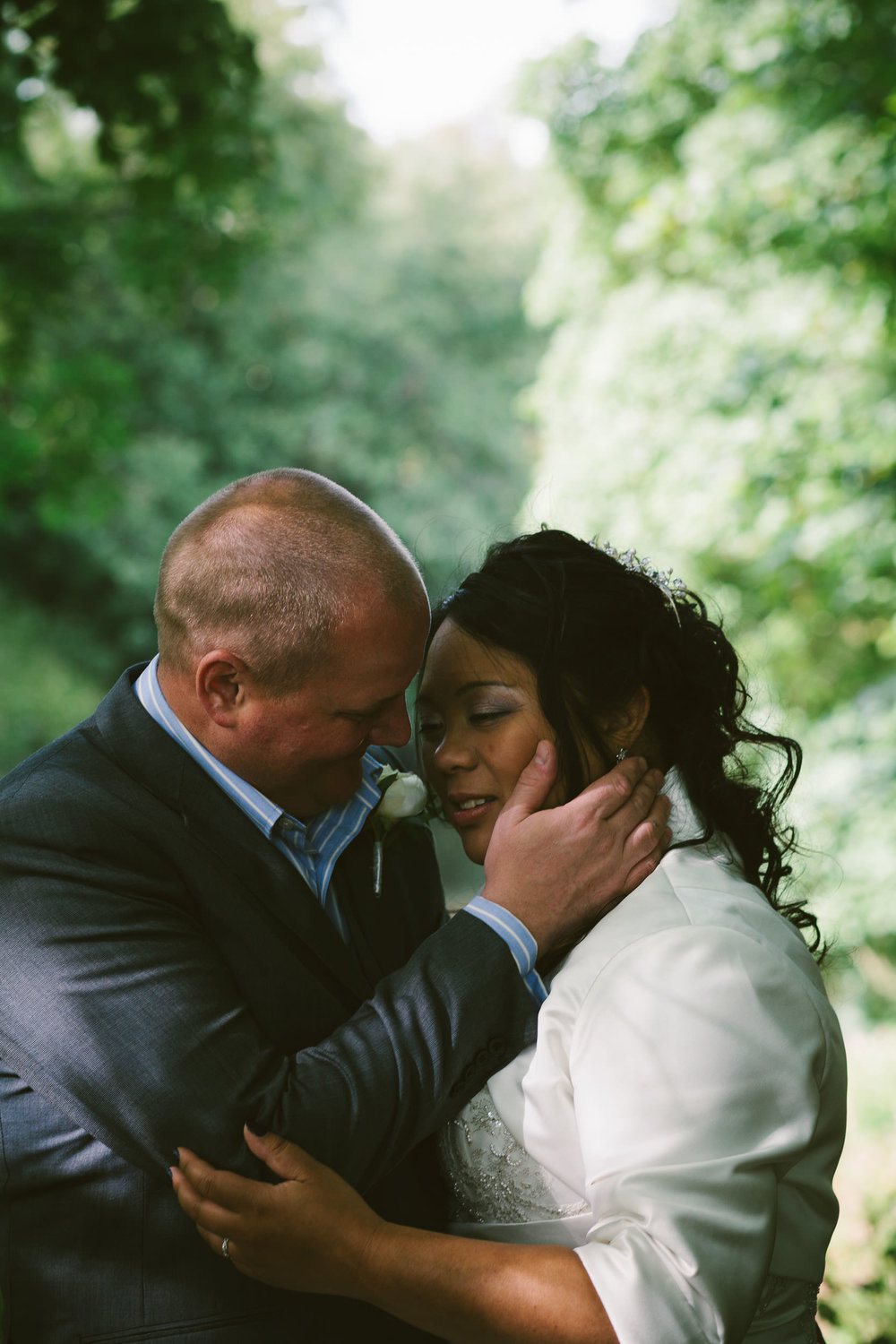 Bride and groom tenderly kiss in woodland