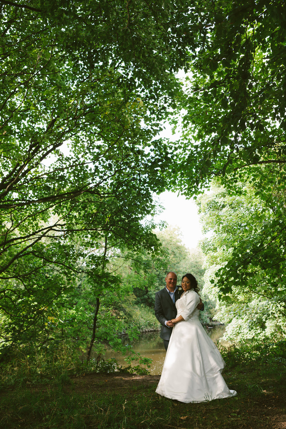 Bride and groom pose under canopy of green trees