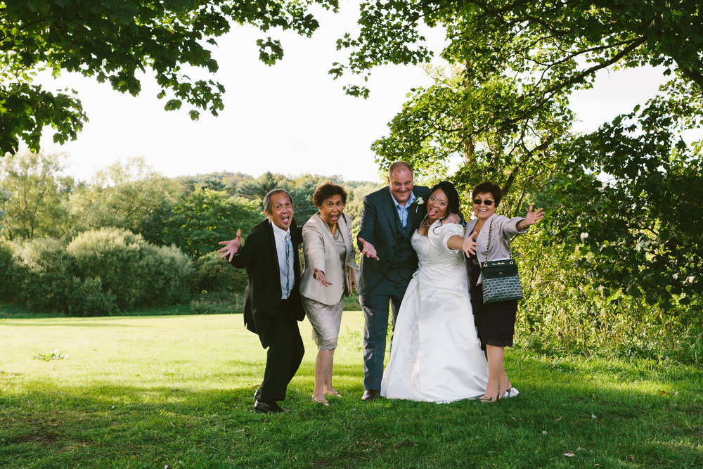 Bride, groom and guests pull funny face during wedding photos