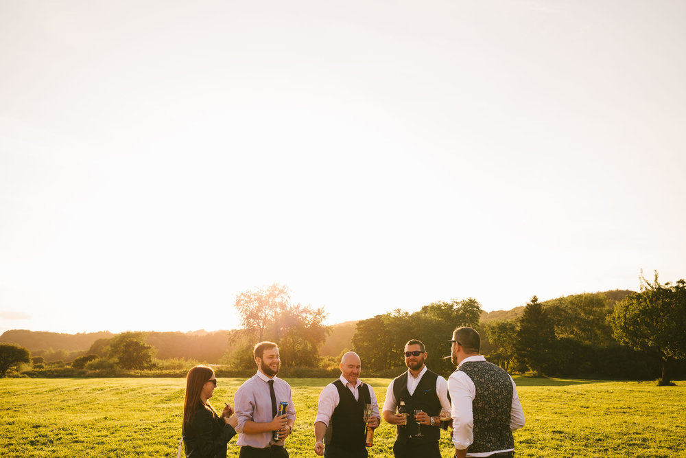 Wedding guests laugh and drink beer outdoors in the golden sun