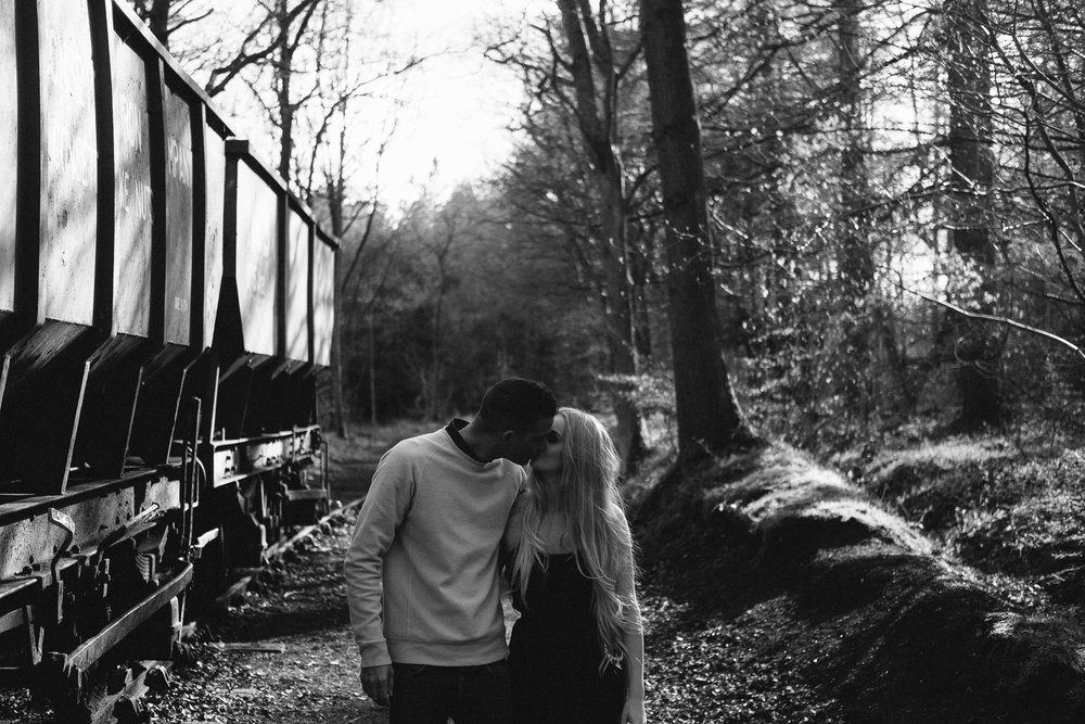 A black and white photo of a couple kissing near a goods train in a wood