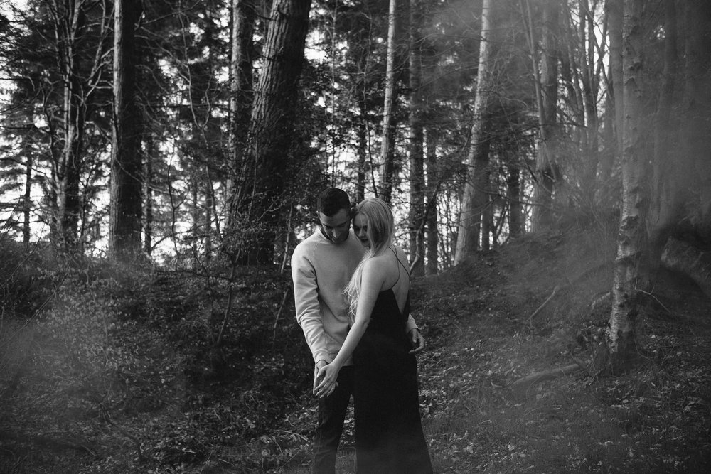 A black and white photo of a couple holding each other close in woodland while smoke drifts around them