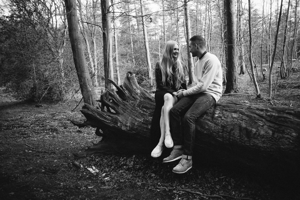 A black and white photo of a couple sitting on a felled tree and chatting in a forest