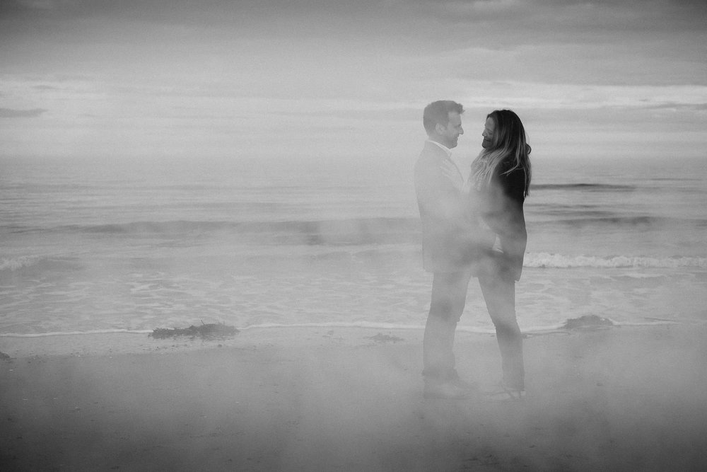 A black and white photo of a couple holding each other on a beach wreathed in smoke