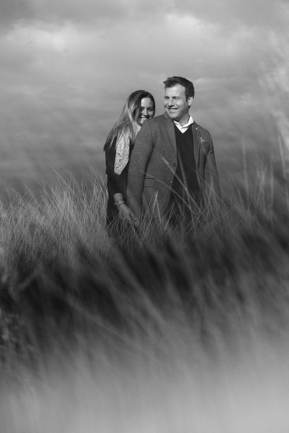A black and white photo of a couple cuddling with out of focus long grass blowing in the wind