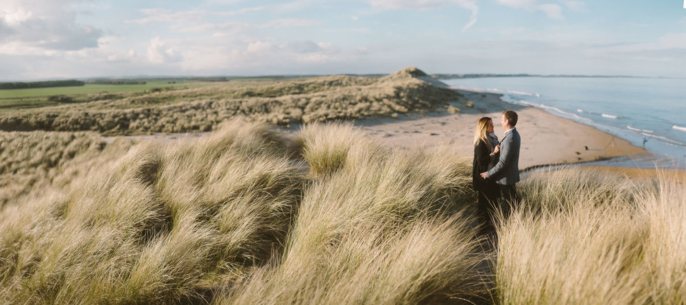 A panoramic photograph of a couple cuddling while standing on a large grass covered sand dune with the Northumberland coast stretching out behind them