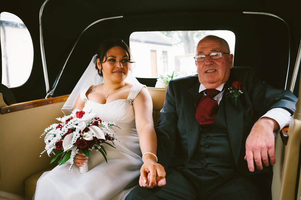 Bride holding dad's hand in the back of the wedding car